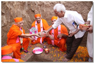 Acharya Swamishree places the bricks in the ground