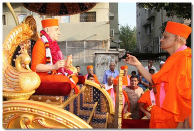 Acharya Swamishree performs aarti to Jeevanpran Swamishree seated on a chariot at the entrance of Shree Swaminarayan Tower
