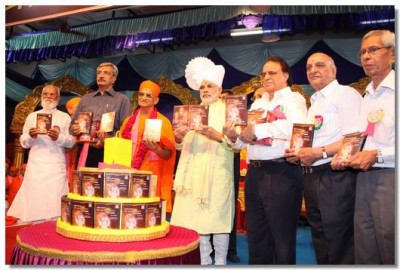 Acharya Swamishree and Shree Narendrabhai Modi and guest with the Serial DVDs