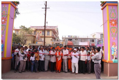 Acharya Swamishree and main dignatories of Sukhpur cut the ribbon to mark the opening of the new gate in Sukhpur