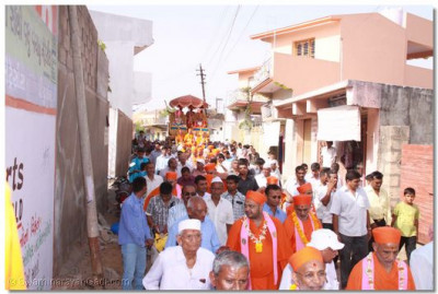 The procession passes through the narrow streets of Sukhpur