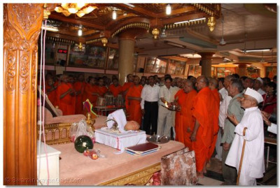 Acharya Swamishree, sants, and disciples perform aarti