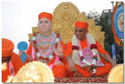 Divine darshan of Jeevanpran Swamibapa and Acharya Swamishree seated on a chariot