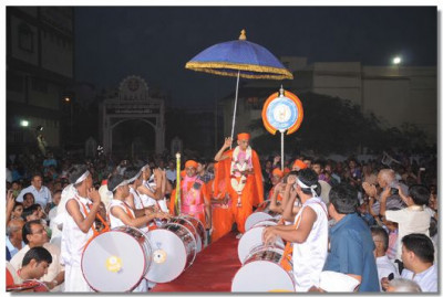 Acharya Swamishree showers His blessings as He walks to the stage
