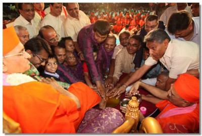 Sants and disciples perform the panchamrut snan ceremony to Acharya Swamishree's lotus feet