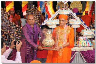 A ceremonial golden urn is presented to Acharya Swamishree Maharaj on this auspicious occasion