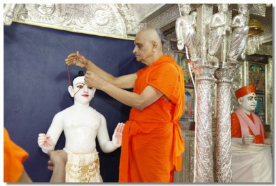 Acharya Swamishree prepares Lord Swaminarayan for the patotsav ceremony
