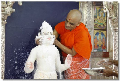Acharya Swamishree lovingly puts sugar on Lord