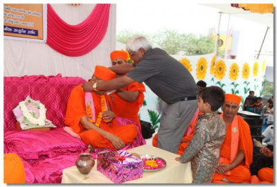 Salim Molu garlands Acharya Swamishree at the start of the special assembly