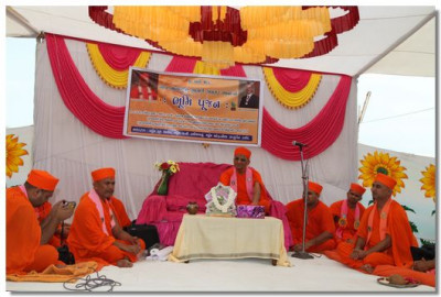 Acharya Swamishree and sants give darshan on a stage