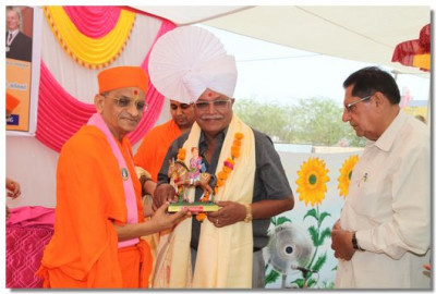 Acharya Swamishree presents a paag and memento to Salim Molu
