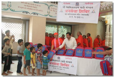 Acharya Swamishree and MLA Shree Mangalprabhat Lodha hand out school bags to children of Mumbai