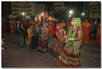 Disciples in traditional dresses take part in the raas