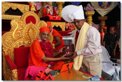 Shree Harshbhai Vadilal Brahmbhatt, Deputy leader of BJP, receives a memento from Acharya Swamishree