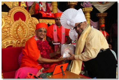 ShreeKentanbhai M Bhatt, Chartered Accountant, receives a memento from Acharya Swamishree