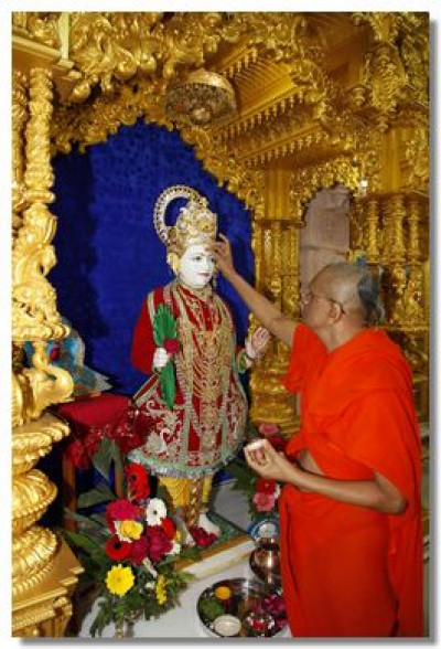Acharya Swamishree commences the patotsav ceremony by applying a chandlo to Lord Swaminarayan