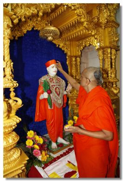 Acharya Swamishree applies a chandlo on Jeevanpran Swamibapa