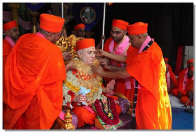 Acharya Swamishree offers a golden necklace to Jeevanpran Swamibapa