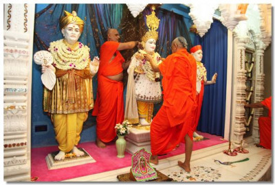 Acharya Swamishree puts a garland on Shree Ghanshyam Maharaj
