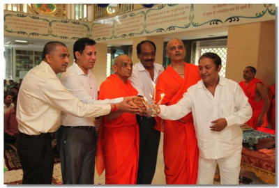 Acharya Swamishree and guests perform aarti to the Lord