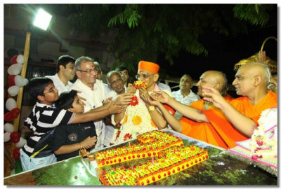 Sants and disciples offer cake to Acharya Swamishre