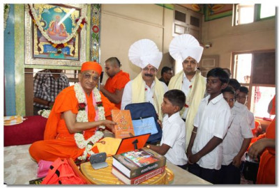 Acharya Swamishree gives school bags to the children of Veer Bhagat Singh Primary School