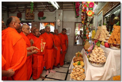 Acharya Swamishree and sants perform annakut aarti