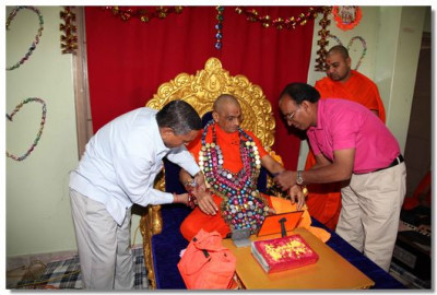 Disciples put a garland of confectionary onto Acharya Swamishree