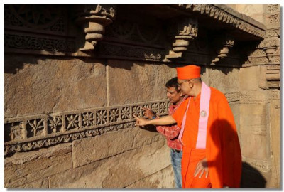 Acharya Swamishree examines the carvings on the walls