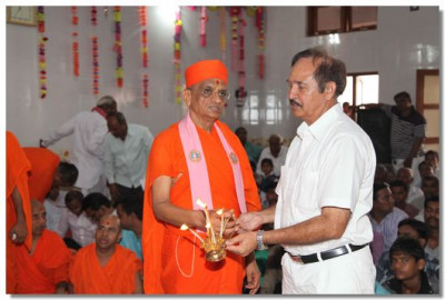 Acharya Swamishree and a disciple perform aarti