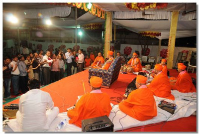 Disciples perform aarti to Acharya Swamishree before the start of the performances
