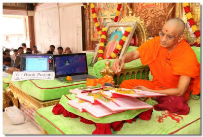 Acharya Swamishree concecrates the accounts books during the chopda poojan ceremony