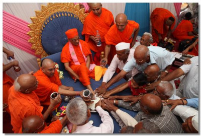 Sants and disciples performs the panchamrut snaan ceremony to Acharya Swamishree
