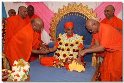Flower bands are put on Acharya Swamishree's wrists