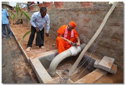 Acharya Swamishree opens the tap to the water irrigation into the gardens