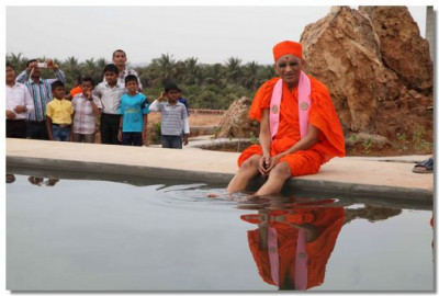 Acharya Swamishree gives darshan at the water tank