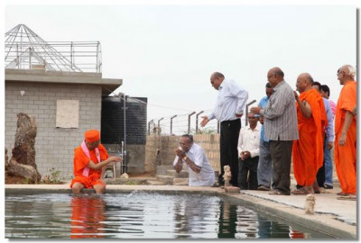Acharya Swamishree showers disciples with water