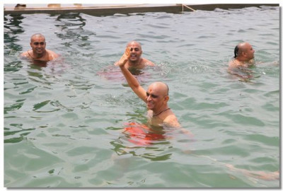 Acharya Swamishree and sants swimming in the pool