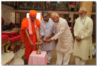 Acharya Swamishree and the principal directors of Hindustan Samachar light a flame to mark the auspicious opening of the convention