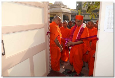 Acharya Swamishree cuts a ribbon to open the newly renovated store in the compound of Maninagar Mandir