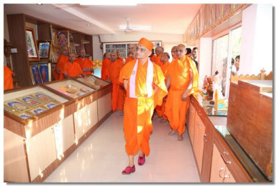 Acharya Swamishree looks through the store of religious articles for sale