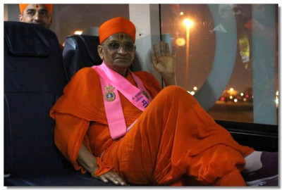 Acharya Swamishree Maharaj gives darshan on the bus to the terminal building