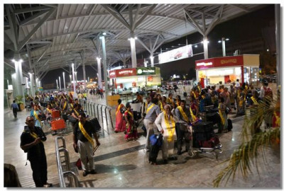 Pilgrims wait for the coach in Delhi airport