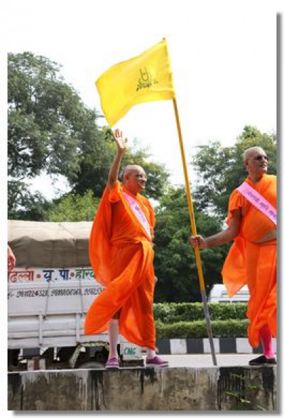 Acharya Swamishree Maharaj waves as each coach passes by