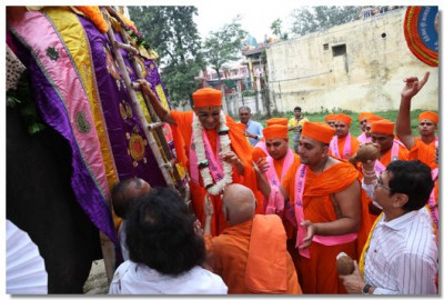 Acharya Swamishree climbs onto the elephant