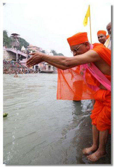 Acharya Swamishree pours water into the sacred river