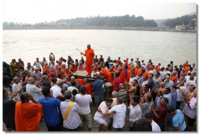 Acharya Swamishree showers water over sants and disciples