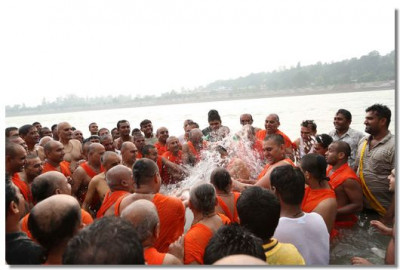Acharya Swamishree showers water over everyone