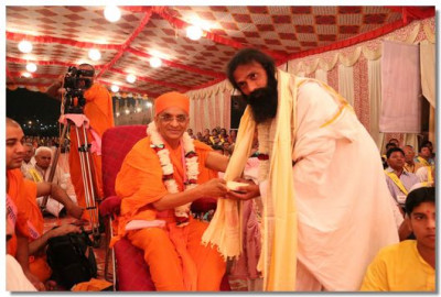 Acharya Swamishree gives prasad to a local chief priest
