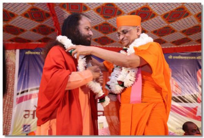 Acharya Swamishree garlands H.H. Muniji
